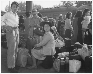 Families of Japanese ancestry awaiting a train which will take them to the Merced Assembly Center
