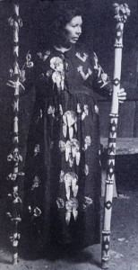 "Essie Parrish holding sacred staffs with pendants.. She was the Yomta (""Song,"" a medicine woman's title) of the Kashaya Pomo. Her ceremonial dress is adorned with abalone pendants."