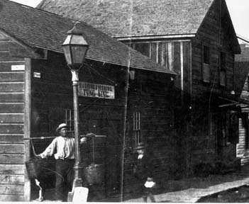 Chinese man holding buckets in front of building. A slice of Eureka's Chinatown in 1885. The sign in the background advertises Washing and Ironing ...