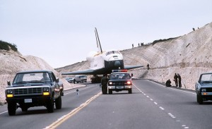 Space Shuttle Enterprise passes through a hillside cut to clear its wingspan, at Vandenberg AFB (1985).